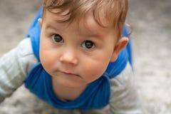 Le garçon se trouve sur son estomac sur le tapis et les rampements images stock