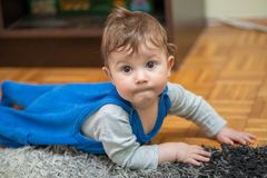 Le garçon se trouve sur son estomac sur le tapis et les rampements image stock