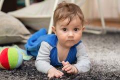Le garçon se trouve sur son estomac sur le tapis et les rampements photographie stock libre de droits