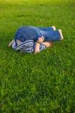 Le garçon se trouve sur une herbe Image stock