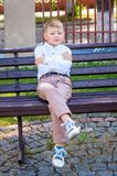 Le garçon seul est attristé, s'asseyant sur le banc Le garçon offensé est a image stock
