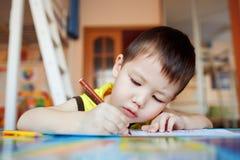 Le garçon soigneusement et dessine attentivement dans un special photo libre de droits
