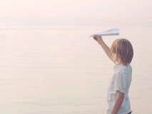 Le garçon solitaire joue avec son papier d'avion de jouet Photo stock