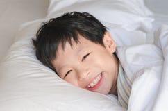 Le garçon sourit après se réveillent sur le lit Photographie stock libre de droits