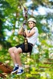 Le garçon sportif, jeune, mignon dans le T-shirt blanc passe son temps dans le parc de corde d'aventure dans le casque et l'équip images libres de droits