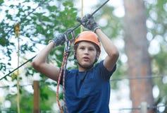 Le garçon sportif, jeune, mignon dans le T-shirt blanc passe son temps dans le parc de corde d'aventure dans le casque et l'équip images stock