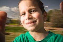 Le garçon sur joyeux vont rond photographie stock