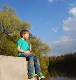 Le garçon sur l'eau potable de rivière Images libres de droits