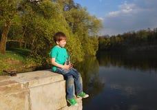 Le garçon sur l'eau potable de rivière Photographie stock libre de droits