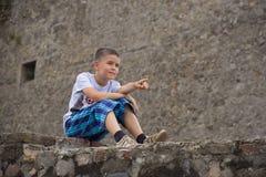 Le garçon sur la barrière en pierre Photographie stock