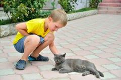 Le garçon sur la rue choyant un chat britannique gris Photo stock