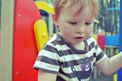 Le garçon sur le terrain de jeu Photographie stock