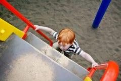Le garçon sur le terrain de jeu en parc Photographie stock libre de droits