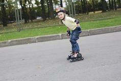 Le garçon sur les lames de rouleau Images libres de droits