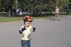 Le garçon sur les lames de rouleau. Images stock