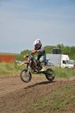 Le garçon sur un petit MX de moto saute dans la descente Photos libres de droits