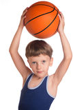 Le garçon a tenu une boule de basket-ball au-dessus d'une tête Image stock