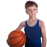 Le garçon a tenu une boule de basket-ball sur une hanche Photos stock