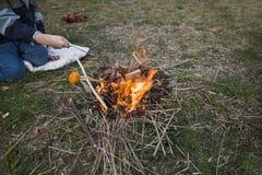 Le garçon tient des morceaux de jambon au-dessus du feu la nourriture au champ sur le feu images stock