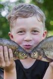 Le garçon tient la brème de deux poissons Image libre de droits