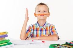 Le garçon tient le crayon entre le nez et la bouche photo libre de droits