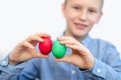 Le garçon tient les oeufs colorés Oeuf vert et rouge dans les mains du garçon Préparations pour Pâques photographie stock libre de droits