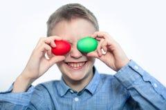 Le garçon tient un oeuf rouge et vert Oeufs de pâques Préparation pour les vacances closeup images stock