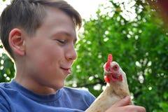 Le garçon tient un poulet blanc dans des ses mains et l'embrasse photographie stock libre de droits