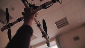 Le garçon tient un quadrocopter qu'il a assemblé dans sa main banque de vidéos
