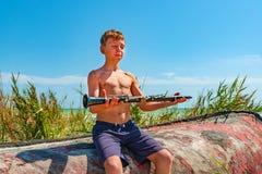 Le garçon tient une clarinette noire dans des ses mains, comprenant le zen se reposant sur un vieux bateau en bois sur la plage images stock