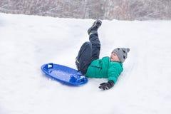 Le garçon tombe roulement vers le bas une colline sur la soucoupe en neige Modélisation dynamique de caractère photographie stock libre de droits