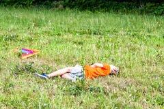 Le garçon a totalement épuisé avoir ensuite l'amusement pilotant un cerf-volant en été photographie stock