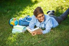 Le garçon très mignon et jeune en verres ronds et la chemise bleue lit le livre se trouvant sur l'herbe à côté du sac à dos et du photo stock
