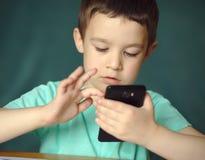Le garçon utilise le smartphone Photo stock