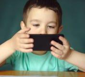 Le garçon utilise le smartphone Photographie stock libre de droits
