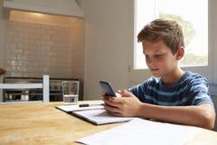Le garçon utilise le téléphone portable tout en faisant le travail à la table de cuisine photos stock
