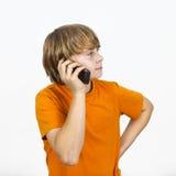 Le garçon utilise son téléphone portable Photos libres de droits