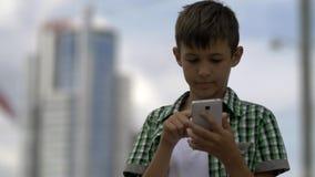 Le garçon utilise le téléphone, cadrans un message, et maintient dans la correspondance photos libres de droits