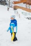 Le garçon va chercher un lecteur sur une pente de neige. photographie stock