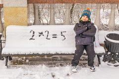 Le garçon vilain décide incorrectement un exemple sur un banc couvert de neige Image stock