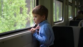 Le garçon voyage par chemin de fer et regarde la fenêtre, observant les objets mobiles en dehors de la fenêtre Déplacement avec banque de vidéos