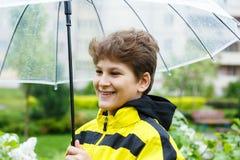 Le gar?on dans l'imperm?able jaune tient le parapluie transparent pendant la pluie Temps pluvieux au ressort photos stock