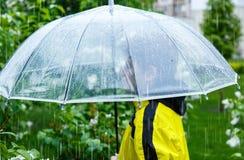 Le gar?on dans l'imperm?able jaune tient le parapluie transparent pendant la pluie Temps pluvieux au ressort photographie stock libre de droits