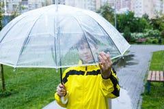 Le gar?on dans l'imperm?able jaune tient le parapluie transparent pendant la pluie Temps pluvieux au ressort image libre de droits