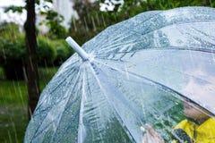Le gar?on dans l'imperm?able jaune tient le parapluie transparent pendant la pluie Temps pluvieux au ressort photos libres de droits