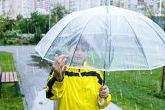 Le gar?on dans l'imperm?able jaune tient le parapluie transparent pendant la pluie Temps pluvieux au ressort, image libre de droits
