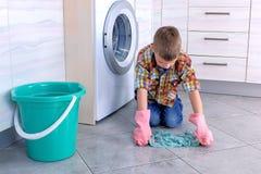 Le gar?on dans les gants en caoutchouc lave le plancher dans la cuisine Les fonctions ? la maison de l'enfant photographie stock libre de droits
