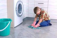 Le gar?on dans les gants en caoutchouc lave le plancher dans la cuisine Les fonctions ? la maison de l'enfant image libre de droits