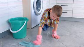 Le gar?on dans les gants en caoutchouc lave le plancher dans la cuisine Les fonctions ? la maison de l'enfant banque de vidéos