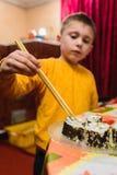 Le gar?on de l'adolescence prend le rouleau de sushi du plat pour manger photos stock
